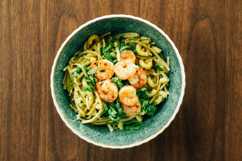A bowl of noodles with spinach and shrimp on a wood table