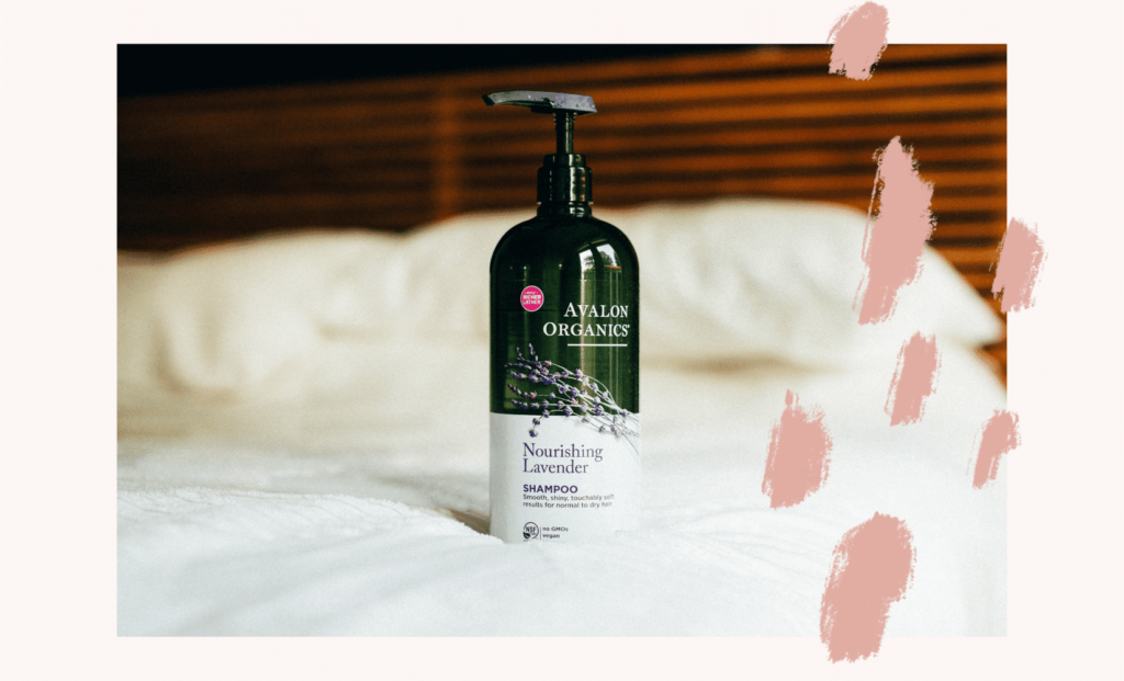 32 ounce pump Avalon organics shampoo on a clean white bed with natural wood background. Photo is on top of pink color with pink brush detailing.